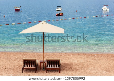 Holiday, travel and vacation concept. The empty beach with two chairs and umbrella. Sea with boats #1397805992