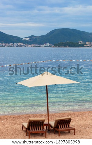 Holiday, travel and vacation concept. The empty beach with two chairs and umbrella. Sea with boats and mountains in a background #1397805998