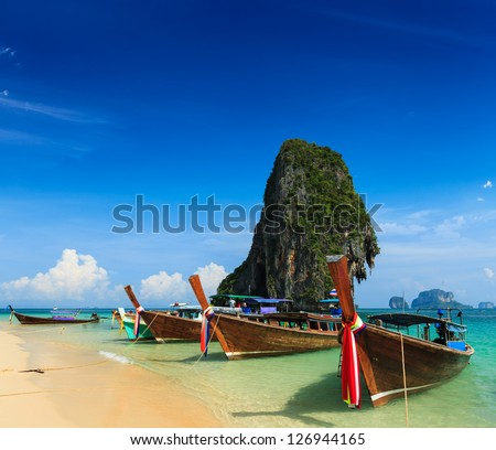 Holiday vacation concept background - Long tail boat on tropical beach with limestone rock, Krabi, Thailand