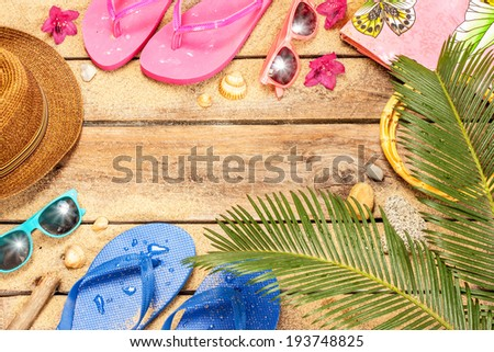 Holiday (vacation) tropical beach background layout with free text space. Palm tree leaves, sand, exotic flowers, sunglasses and flip flops on vintage wood - poster design.