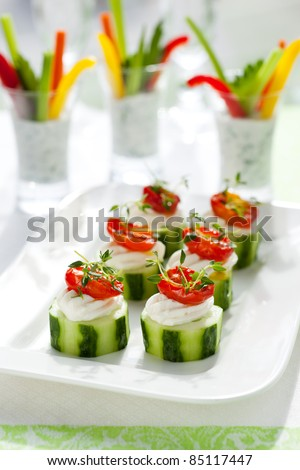 Holiday vegetable appetizers.Cucumber s with soft cheese and sun dried tomatoes and vegetable sticks with dip - stock photo
