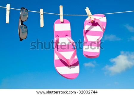 Holiday washing line against blue sky with flip flops and sunshades - reflection of beach in sunglasses
