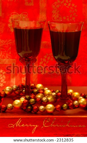 Holiday Wine - Two glasses of merlot wine sit among the holiday decorations. - stock photo
