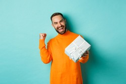 Holidays and celebration concept. Excited man receiving gift, looking happy at present and smiling, standing over blue background