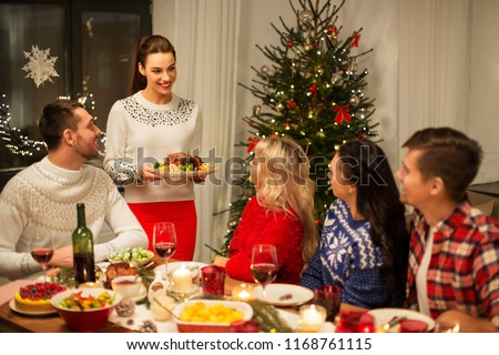 holidays and celebration concept - happy friends having christmas dinner at home #1168761115