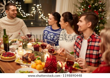 holidays and celebration concept - happy friends having christmas dinner at home and eating #1198890448