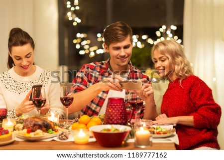 holidays and celebration concept - happy friends having christmas dinner at home and photographing food by smartphone #1189777162