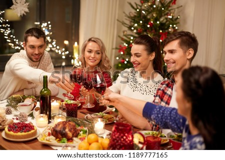 holidays and celebration concept - happy friends having christmas dinner at home, drinking red wine and clinking glasses #1189777165