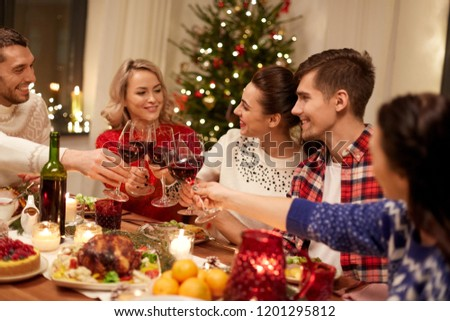 holidays and celebration concept - happy friends having christmas dinner at home, drinking red wine and clinking glasses #1201295812