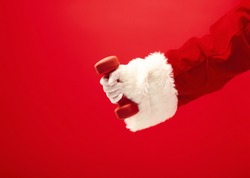 Holidays and celebrations, New year, Christmas, sports, bodybuilding, healthy lifestyle - Santa Claus with dumbbells. Isolated on red background.