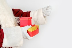 Holidays and Christmas concepts. Santa Claus holds a gift in his hand, and the second shows a fig. Isolated on white