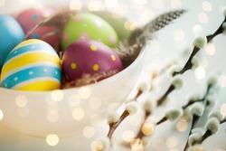 holidays and object concept - colored easter eggs with quail feathers in bowl and pussy willow branches over bokeh lighs