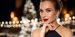 holidays and people concept - beautiful woman in black with red lips over christmas tree lights background