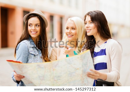 holidays and tourism concept beautiful girls looking for direction in the city