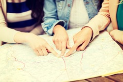 holidays and tourism concept - women with tourist map in the city