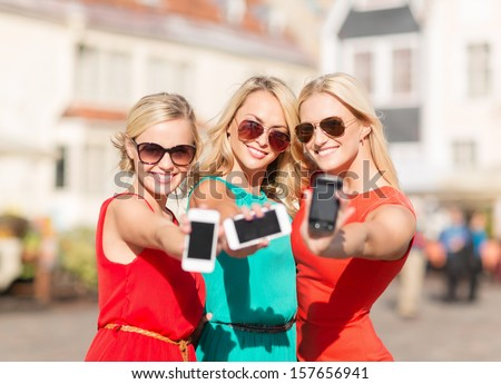 holidays and tourism modern technology concept beautiful blonde girls with smartphones in the city