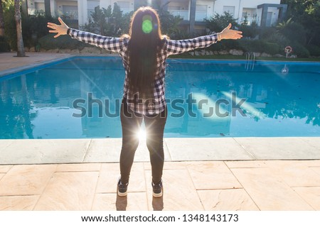 Holidays and vacation concept - Back view of woman at resorts near swimming pool on summer vacations. #1348143173