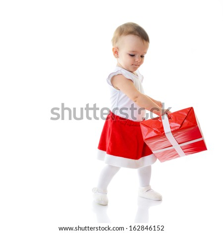 Holidays, baby girl dancing with presents, christmas, birthday, new year, x-mas concept - happy child girl with gift boxes