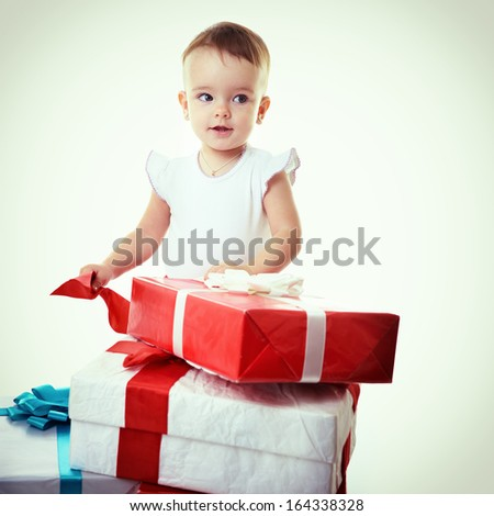 Holidays, baby girl opening box with presents, christmas, birthday, new year, x-mas concept - happy child girl with gift boxes, toned