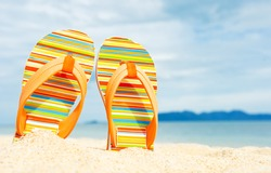 Holidays Background. Beach sandals on the sandy coast