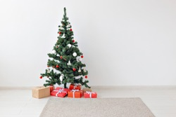 Holidays, celebration and gifts concept - Christmas tree and many present boxes on white indoors with copy space