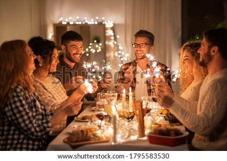 holidays, celebration and people concept - happy friends with sparklers having christmas dinner at home