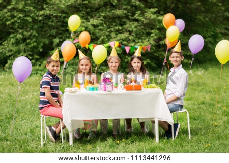 holidays, childhood and celebration concept - happy kids sitting at table on birthday party at summer garden #1113441296