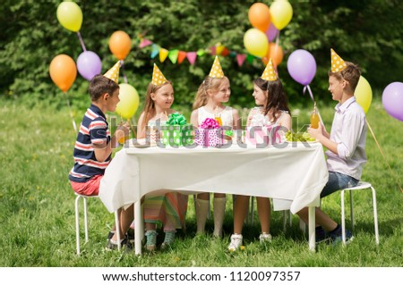 holidays, childhood and celebration concept - happy kids sitting at table on birthday party at summer garden #1120097357