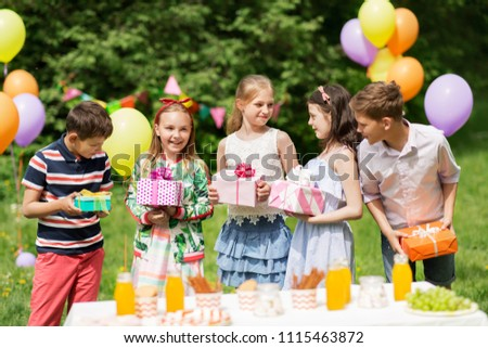 holidays, childhood and celebration concept - happy kids with gifts on birthday party at summer garden #1115463872