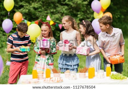 holidays, childhood and celebration concept - happy kids with gifts on birthday party at summer garden #1127678504