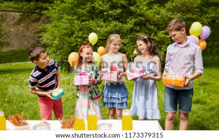holidays, childhood and celebration concept - happy kids with gifts on birthday party at summer garden #1173379315