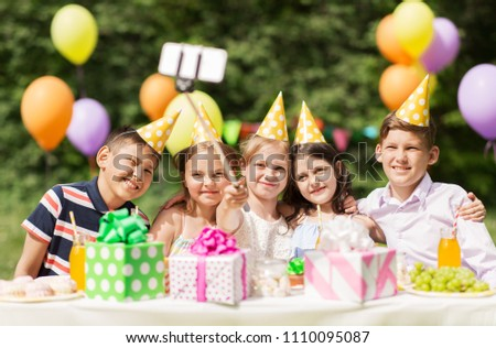 holidays, childhood and technology concept - happy kids taking picture by selfie stick on birthday party at summer garden #1110095087
