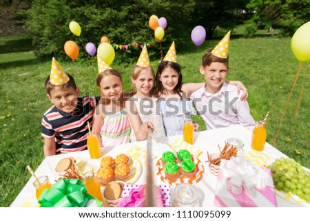 holidays, childhood and technology concept - happy kids taking picture by selfie stick on birthday party at summer garden #1110095099