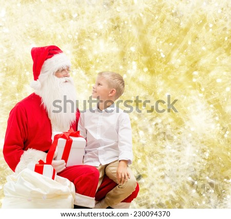 holidays, christmas, childhood and people concept - smiling little boy with santa claus and gifts over yellow lights background