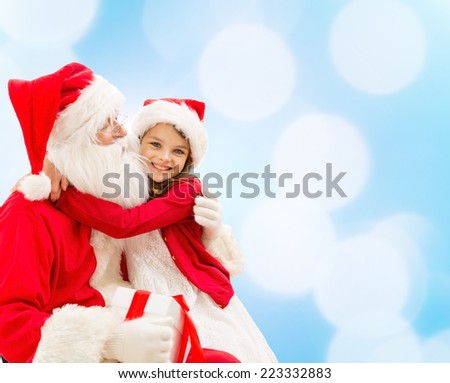 holidays christmas childhood and people concept smiling little girl hugging with santa claus over blue lights background