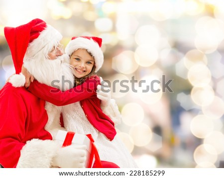 holidays, christmas, childhood and people concept - smiling little girl hugging with santa claus over lights background #228185299