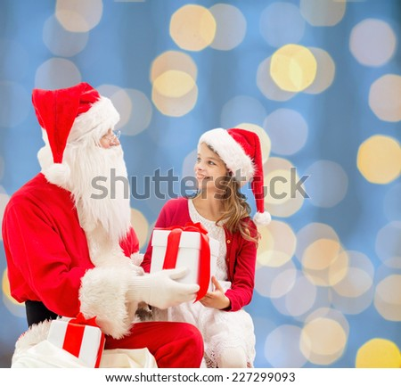 holidays, christmas, childhood and people concept - smiling little girl with santa claus and gifts over blue lights background