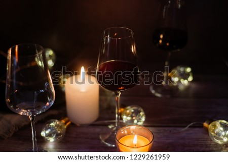 Holidays composition made of glass of red wine, candles and garlands on a dark background #1229261959