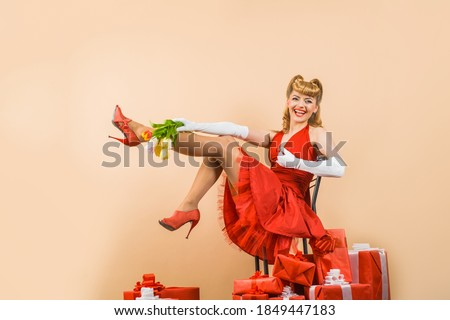 Holidays concept. Pin up woman with present box. Happy New Year. Gift. Happy girl with gifts Retro woman in present boxes. Pin up woman with flowers.