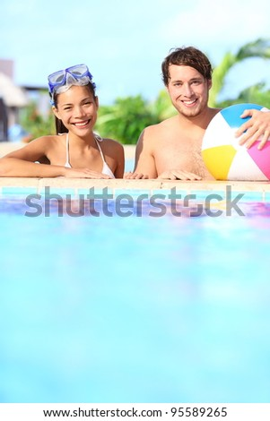Holidays couple in pool having fun in sunny vacation resort under the sun. Young mixed race couple, Caucasian man, Asian woman.