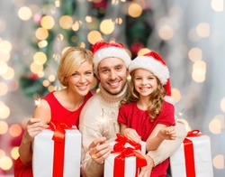 holidays, family and people concept - happy mother, father and little girl in santa helper hats with gift boxes and sparklers over living room and christmas tree background