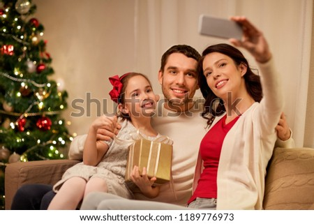 holidays, family and technology concept - happy mother, father and little daughter with christmas gift taking selfie by smartphone at home