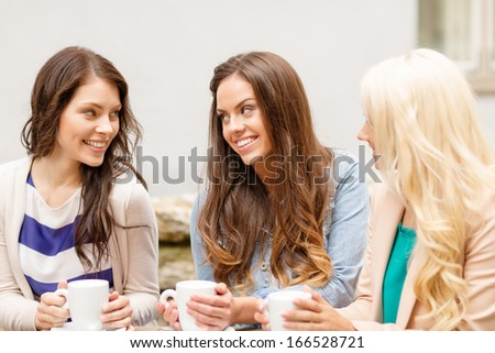 holidays, food and tourism concept - three beautiful girls drinking coffee in cafe