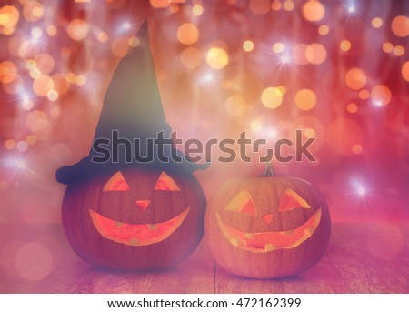 holidays, halloween and decoration concept - close up of carved pumpkins with smiley faces and witch hat on table over lights #472162399