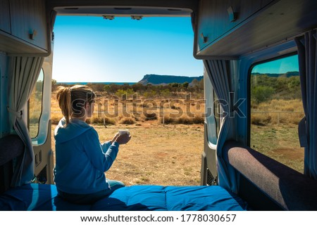 Holidays in Australia, woman having a coffee at the back side of a caravan. Van life, coffee cup on her hands at morning time. Motorhome without logos parked in front of Kings Canyon, NT Australia