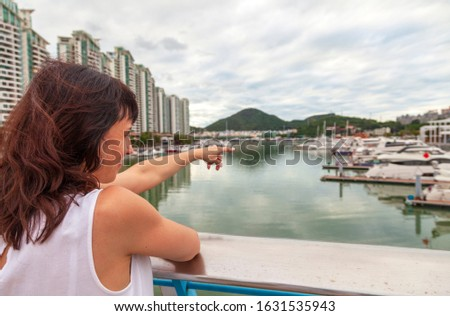 Holidays in Hainan, a girl shows her hand on a beautiful bay in Sanya