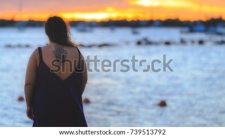 Holidays in Indian ocean witha a sunset in the background with a classic view over sea. Girl with one hamsa tattoo in her back looking and relaxing.