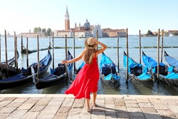 Holidays in Venice. Back view of beautiful girl in red dress enjoying view of Venice Lagoon with the island of San Giorgio Maggiore and gondolas moored.