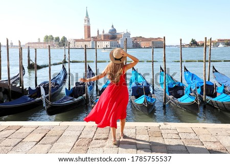 Holidays in Venice. Back view of beautiful girl in red dress enjoying view of Venice Lagoon with the island of San Giorgio Maggiore and gondolas moored. Foto stock ©