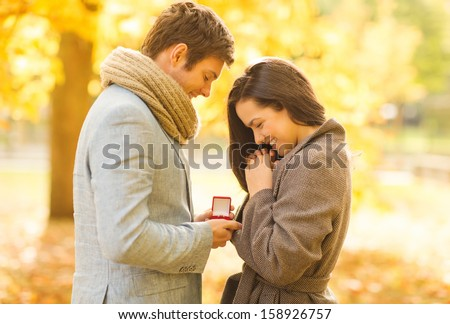 holidays, love, couple, relationship and dating concept - romantic man proposing to a woman in the autumn park